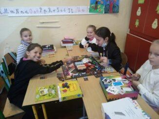 Uczniowie grający w grę planszową.