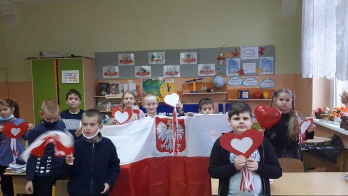 Święto Niepodległości w klasach 2 a i 2 d. Uczniowie ubrani na galowo z kotylionem.