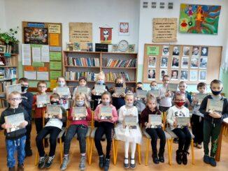 """""""Mała książka-wielki człowiek"""" Dzieci trzymające elementarz."""