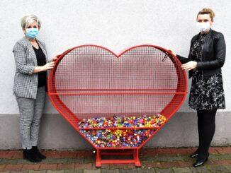 Na zdjęciu dyrektor szkoły i przewodnicząca RR, trzymające wielkie serce, w którym są korki od butelek.
