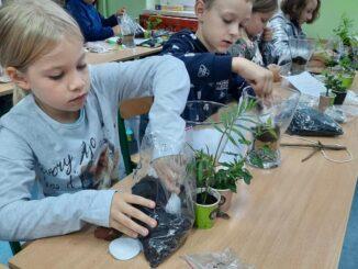 Uczniowie i ich małe ogrody w słojach
