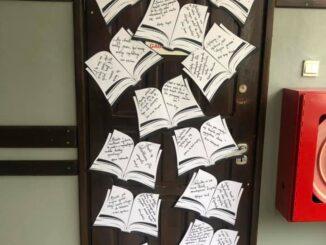 Drzwi wystrojone w tytuły książek i elementy jesienne