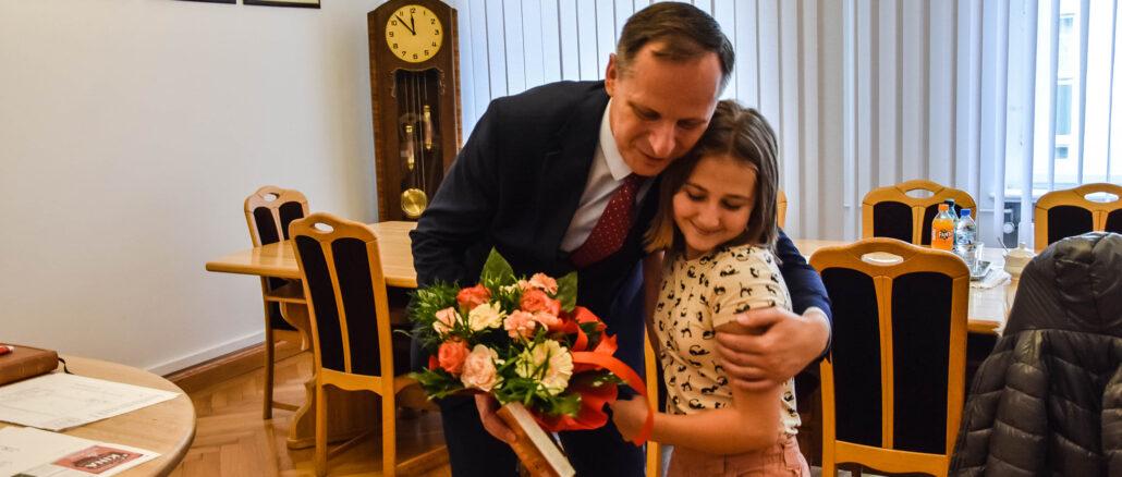 Burmistrz z uczennicą Mają i jej mamą- wrecza nagrodę za sukcesy w tańcu akrobatycznym