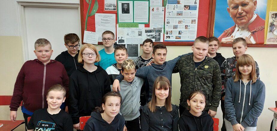 Uczniowie 6a na tle gazetki Szkoła Pamięta